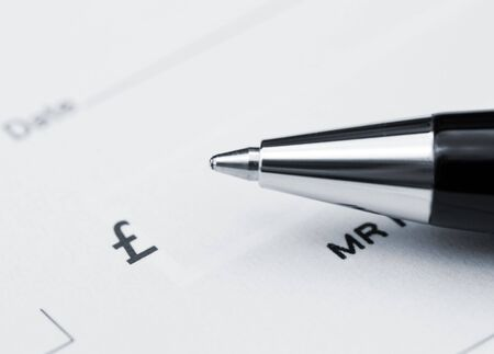 payee: Close-up of pen resting on UK cheque