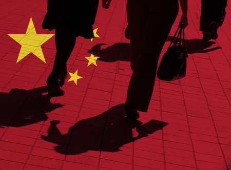 Silhouetted pedestrians overlaid with Chinese flag