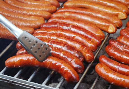Closeup of sausages being turned on grill Stock Photo