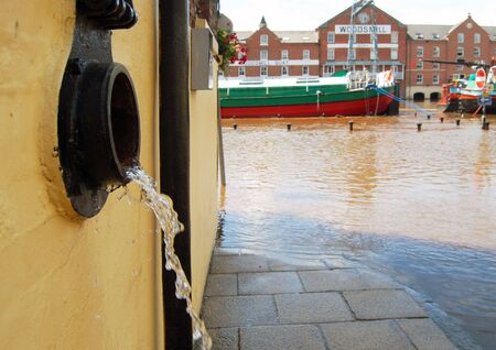 ouse: Closeup of water being discharged from flooded building. River Ouse, York, UK.