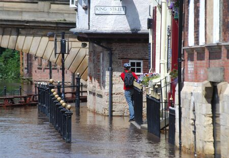 ouse: Male pedestrian hangs on fence to view flooding of River Ouse, York.