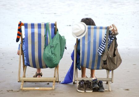 Two holiday makers sit in deckchairs on English beach Stock Photo