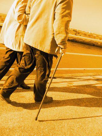 Dos ancianos caminando en el muelle, con efecto de luz amarilla Foto de archivo - 5402091