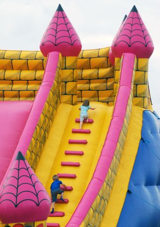 Young children climb steps in inflatable bumper castle photo
