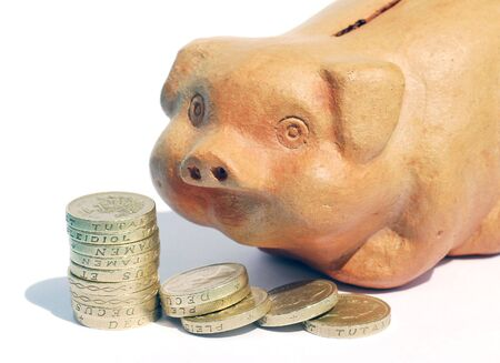 Stack of UK pound coins with terracotta piggy bank photo