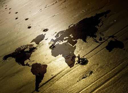 Lone footprints walk across world map in sand Stock Photo