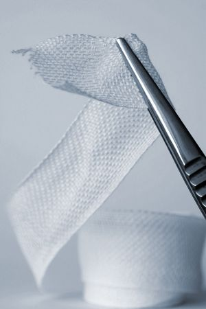 firstaid: Closeup of surgical tweezers holding ribbon bandage