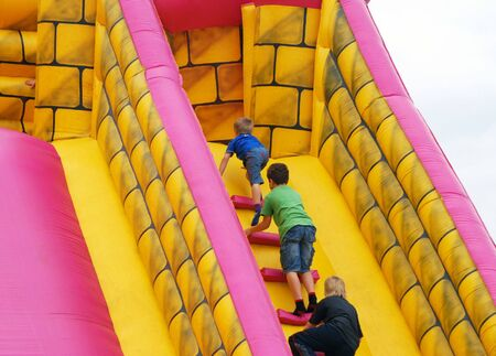 Children climb steps in inflatable bumper castle photo