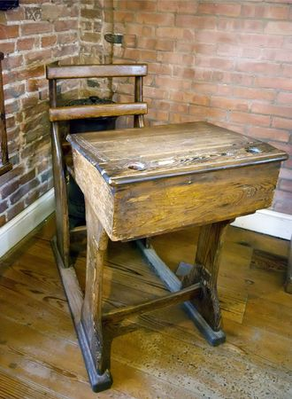 Old wooden school desk in brick wall building Stock Photo
