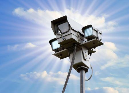 big brother spy: C�mara de seguridad contra el cielo azul nublado con destellos de sol  Foto de archivo