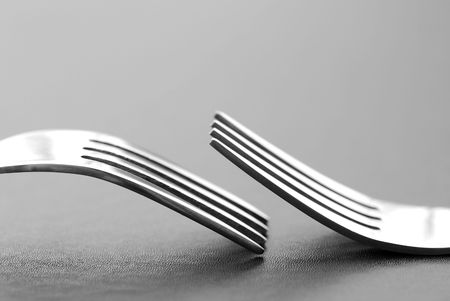 Two dining forks resting on a textured surface photo