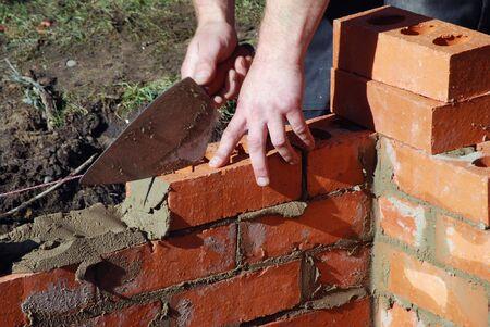 Close up of bricklayer building wall photo