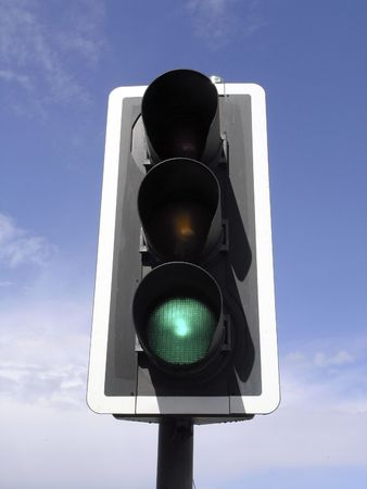 View of green traffic light against cloudy blue sky photo