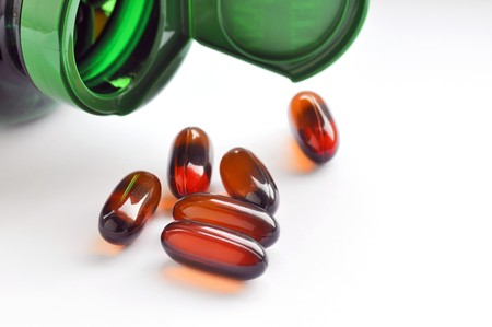 flaxseed: Close up of green bottle with flaxseed oil capsules Stock Photo