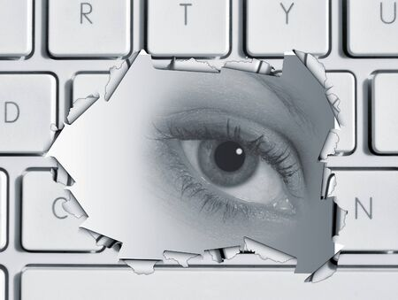 Torn hole in computer keboard revealing watching eye Stock Photo - 7532431