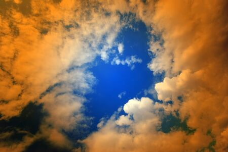 wide angle: Wide angle view of puffy clouds in blue sky overlaid with orange Stock Photo