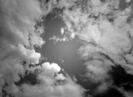 moody: Wide angle view of puffy clouds in black and white