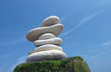 Pile of stones on wooden post against blue sky photo