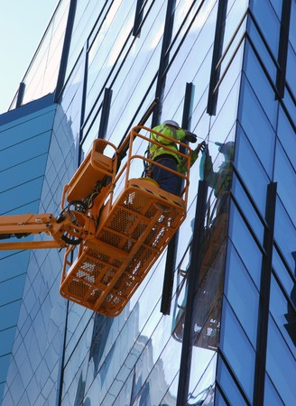 glass building: Construction worker working on glass building exterior