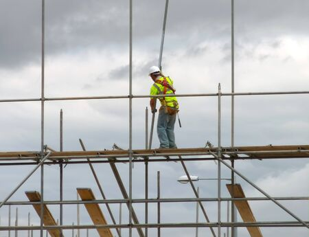 scaffold: Closeup of construction worker assembling scaffold on building site