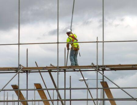 andamios: Detalle del trabajador de construcci�n, montaje de andamios en la creaci�n de sitio