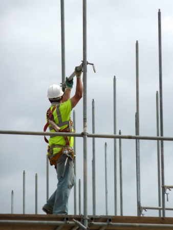 harness: Closeup of construction worker assembling scaffold on building site