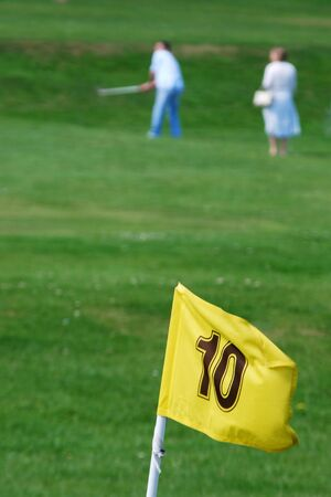 Out of focus golfers with yellow flag photo