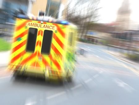 Speeding ambulance flies through city street with zoom blur photo