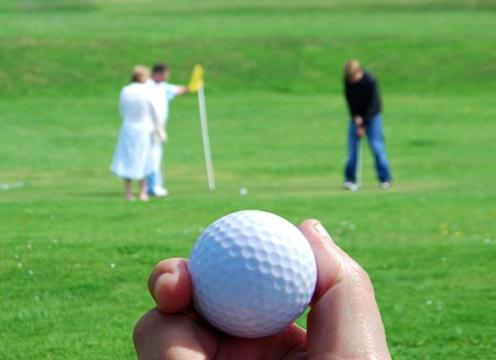 Out of focus golfers with hand holding golf ball photo