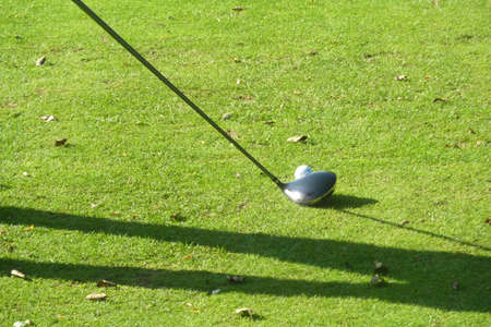 View of golf players shadow with club and ball photo