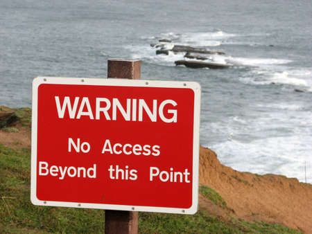 cliff edge: Warning sign on top of cliff edge at Filey Brigg