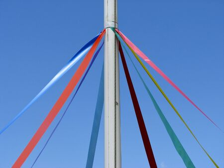 View showing ribbons on Maypole against blue cloudless sky photo