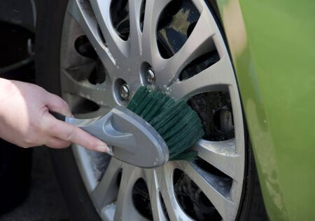 car cleaning: Female washing car using shampoo and brush