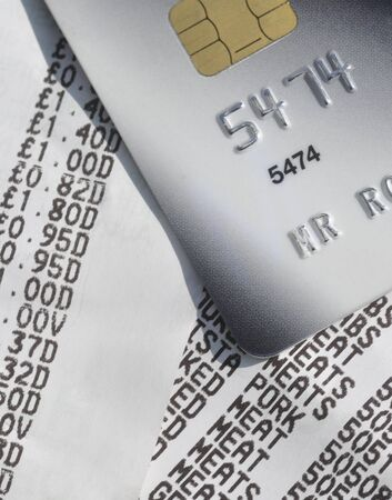 Closeup of credit card resting on supermarket till receipts photo