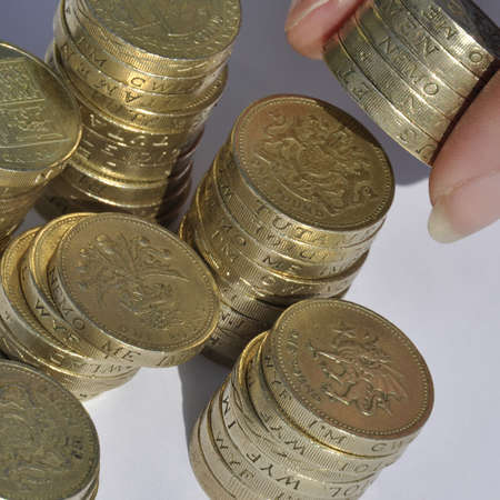Closeup of stacks of pound coins with hand holding coins. photo