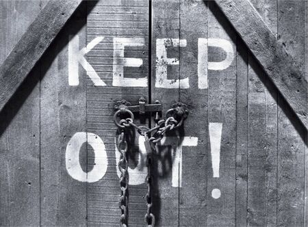 Closeup of Keep Out sign on wooden door photo