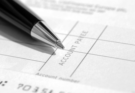 payee: Closeup of pen resting on blank cheque