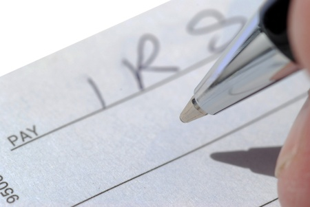payee: Close up of fingers holding pen over cheque to IRS Stock Photo