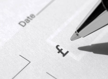 payee: Closeup of pen resting on blank UK cheque