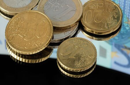 20 euro: Closeup of coins resting on mirror with a reflection of a twenty euro banknote. Stock Photo