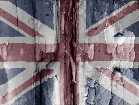 union jack flag: Unusual grunge type image show the British flag overlaid over flaky paint on old wooded door. Faded colors used adds to the effect. Eye catching image has many uses.
