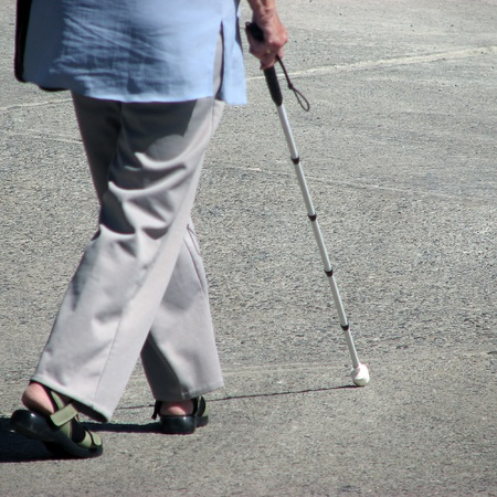 a blind: Elderly woman walking in street using walking stick