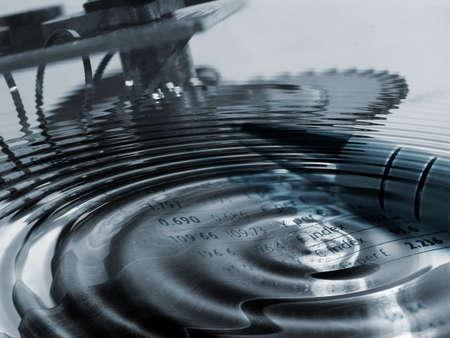 通貨の数字を重ねて水の波紋と時計じかけの部分を示す概念図 写真素材