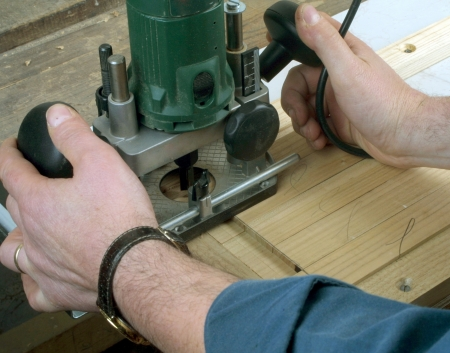 carpenter's sawdust: Male woodworker using an electric routing tool