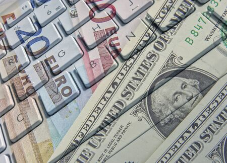 Closeup of laptop keyboard overlaid with Euros and dollar banknotes photo