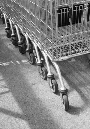convenience store: Line of empty supermarket trollies at local store. Stock Photo