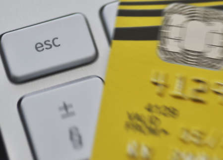 escape key: Zoom effect centered on computer Escape key with blurred credit card   Escaping debt