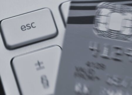 escape key: Zoom effect centered on computer Escape key with blurred credit card.