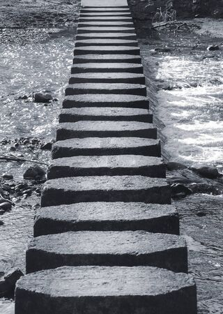 Closeup view of stepping stones crossing river photo