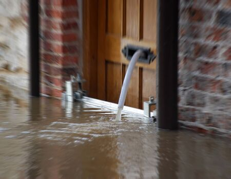 ouse: Water being pumped from property during River Ouse floods in York. Zoom effect applied to water coming from pipe.